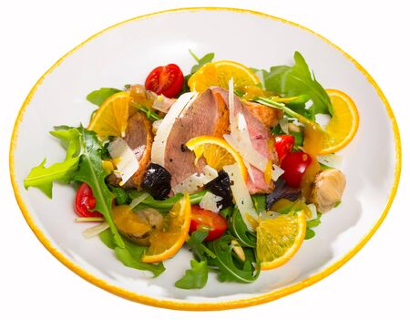 Appetizing poultry salad with duck breast, fresh greens and tomatoes. Isolated over white background