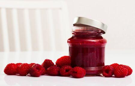 Glass jar of homemade raspberry jam with fresh berries on background
