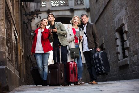 Family of four travellers with luggage reading city map and sightseeing outdoors