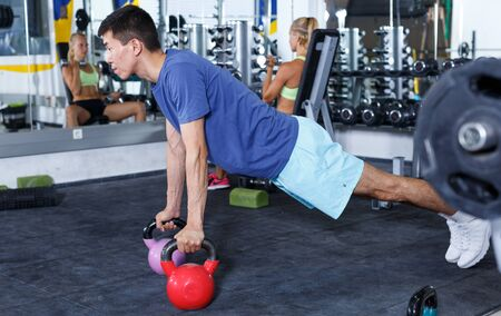 Portrait of strong fitness man exercising with dumbbells in gym