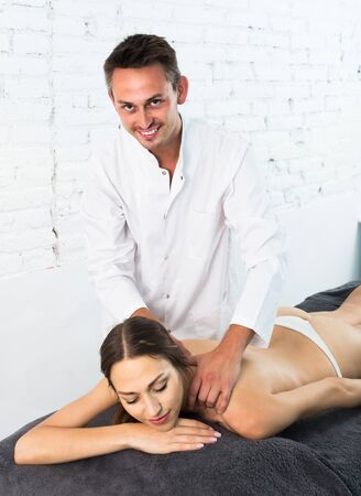 Portrait of young french woman enjoying relaxing massage by professional masseur Zdjęcie Seryjne