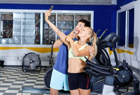 Smiling glad athletic pair making selfie during break in workout session at gym