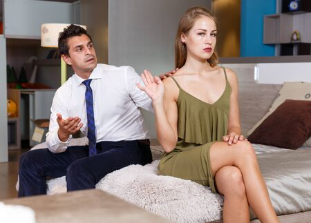 Attractive offended girl sitting on bed and gesturing enough while her husband trying to apologize after quarrel
