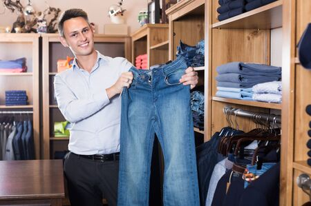 Male is choosing on new jeans in mens clothes store.