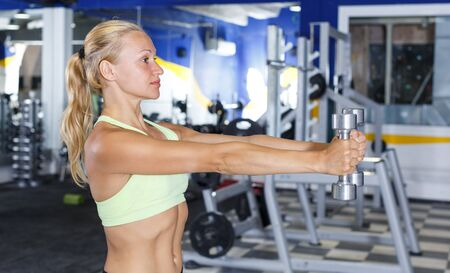 Portrait of sporty woman exercising with dumbbells in gym