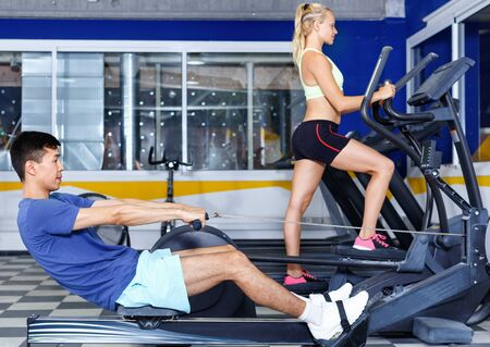 Young smiling friendly  fitness man and woman doing cardio workout on fitness machines at gym