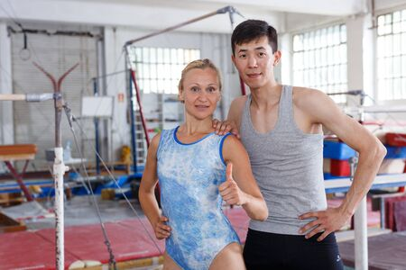 Fit couple man and woman posing near gymnastic equipments in gym