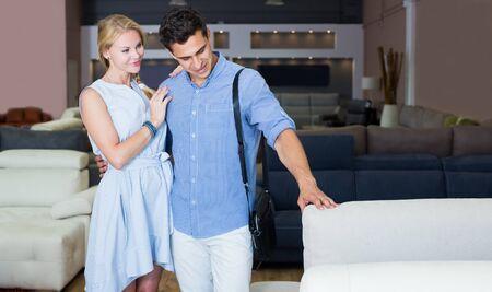 Happy couple are choosing new sofa-transformer in furniture store. Foto de archivo - 131988400