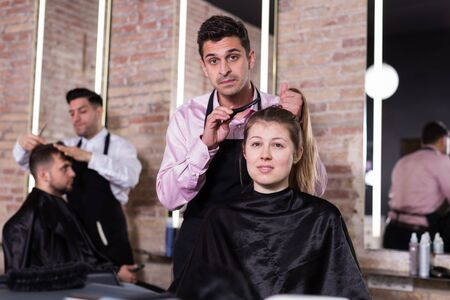 Pleasant dark haired female client sitting in chair while discussing haircut with professional hairdresser