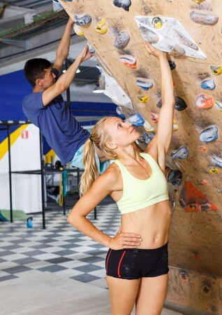 Sporty couple of climbers on joint workout training at bouldering gym Banco de Imagens