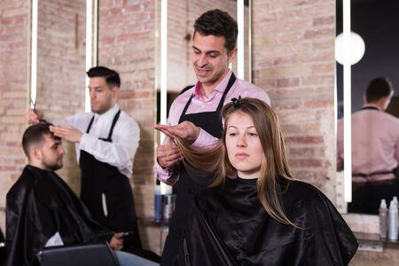 Skilled man hairdresser making hairstyle for young female client in hair studio