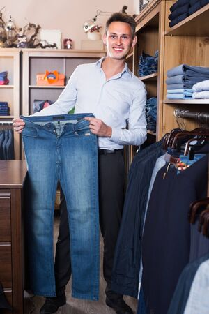 Customer is choosing on new jeans in mens clothes store.