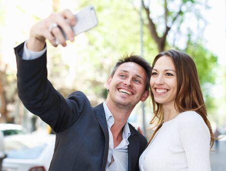 Junger Mann mit seiner Freundin macht Selfie beim Spaziergang durch die Stadt