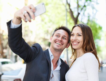 Young man with his girlfriend making selfie while walking around city