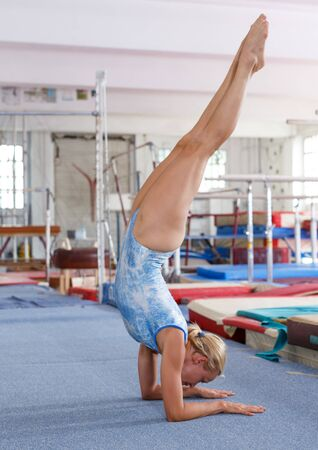 Fit woman training gymnastic elements on floor in acrobatic hall Stok Fotoğraf