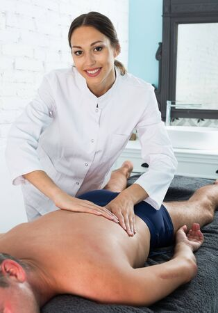 Professional massagist making body procedures in beauty parlor
