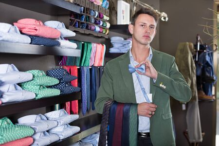 Young happy male customer examining ties in a male cloths store