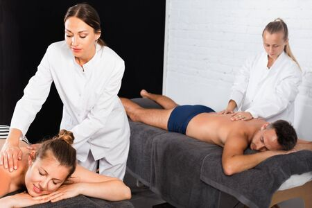 Happy cheerful woman and man enjoying relaxing massage by professional masseuses