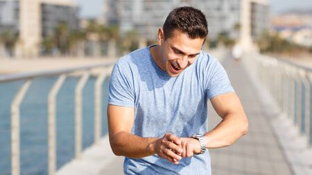 Sporty man looking at fitness wristband checking heart rate monitor