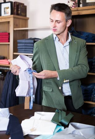 Man shopping assistant offering various clothes in shop 스톡 콘텐츠