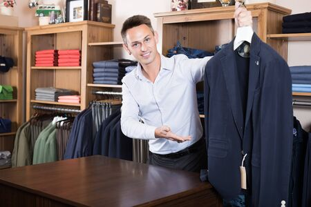 Male shopping assistant offering various cloths in  store 스톡 콘텐츠