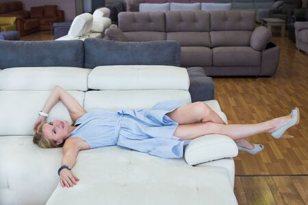 Woman is testing new sofa in furniture store.