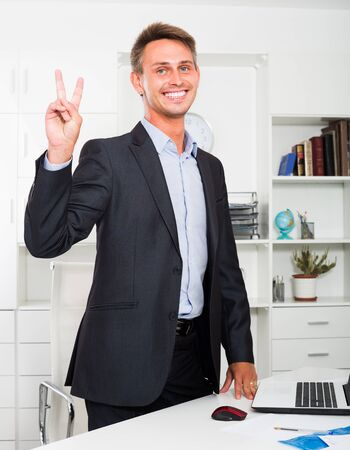 cheerful  smiling young business man in formalwear standing in company office