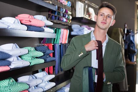 Adult guy deciding on new tie in male cloths store