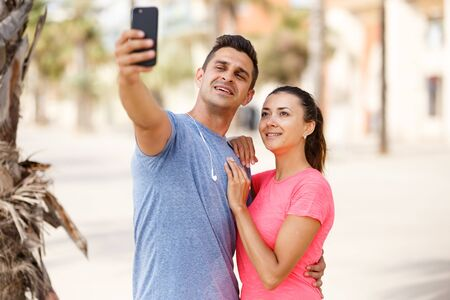 Smiling athletic pair making selfie during break in workout session