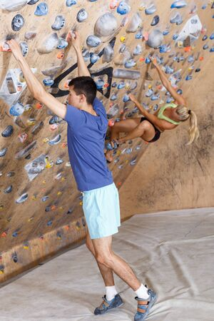 Two confident mountaineers climbing artificial rock wall without belay indoors