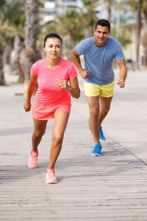 Fit couple dressed in sportswear jogging on street at summer day Imagens