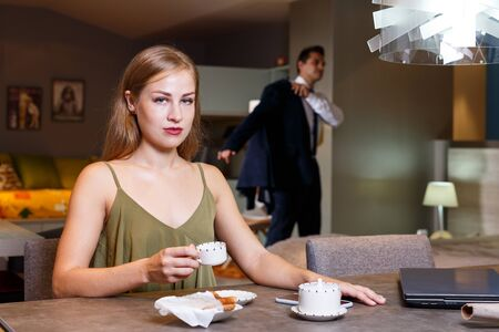 Elegant young woman sitting at home table with cup of coffee on background with man in suit Banco de Imagens