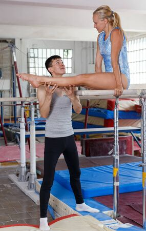 Man coaching woman who doing gymnastic exercises on  parallel bars in gym