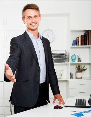 Young cheerful working man satisfied with agreement in company office
