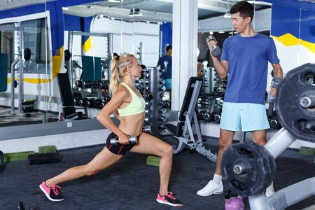 Concentrated athletic people during weightlifting training at fitness center