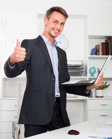 Glad business man in formalwear standing with laptop in hands in company office