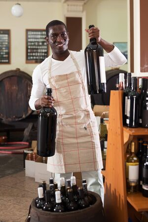 Positive male seller shows two large bottles of wine for purchase at a wine house