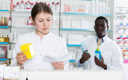 Confident female pharmacist working in drugstore, picking up prescription medicines