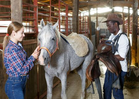 European girl and afro man who work at stable preparing saddle for horse