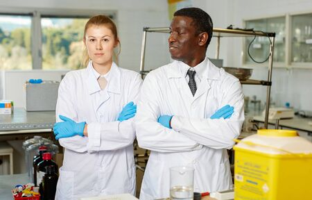 Experienced male and female scientists standing in interior of laboratory