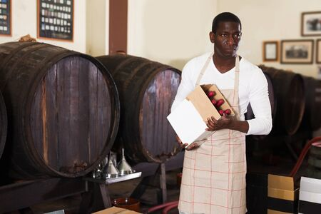 professional young male winemaker holding box with wine bottles standing in wine shop
