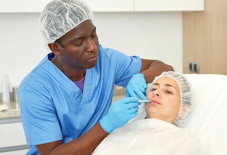 Dermatologist male preparing  woman client before  aesthetic facial procedure  in medical  office