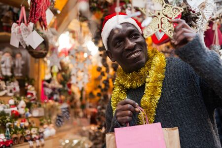 Cheerful African American in Santa hat looking for New Year decorations in traditional street market