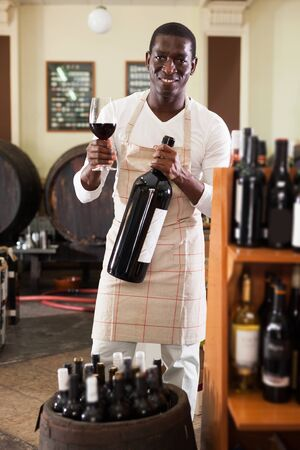 positive afro salesman with wineglass and bottle of wine offering to taste product before purchasing Stok Fotoğraf