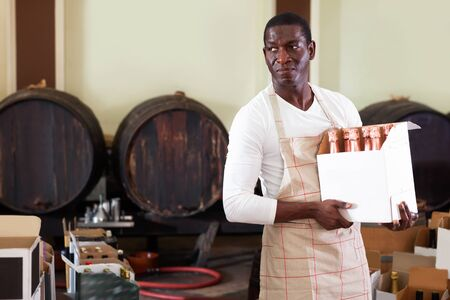 Diligent cheerful smiling afro seller working in wine store, holding box full of bottles with wine