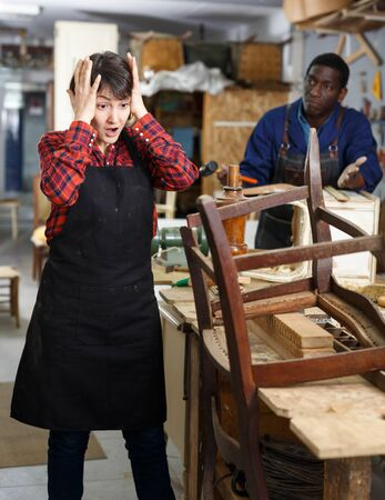 Unhappy woman artisan standing near restoring old chair in woodwork studio