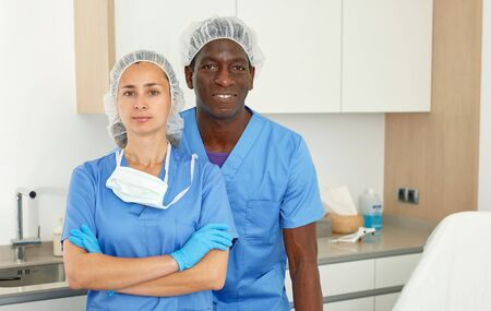 Professional cosmeticians woman and man in uniform in clinic of esthetic cosmetology
