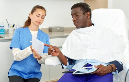 Professional cosmetician woman with papers talking to man before procedure in clinic of esthetic cosmetology