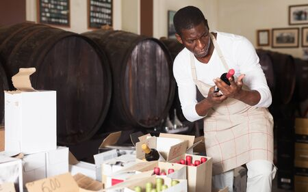 Positive male winemaker inspecting wine bottles in boxes in wine store Stock Photo