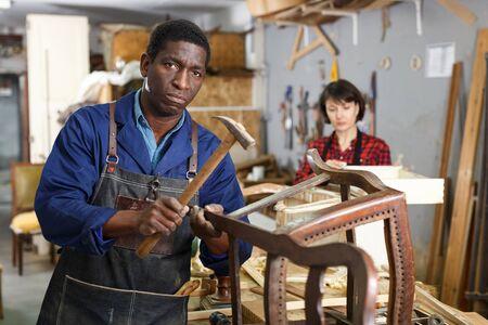 Professional furniture restorer renewing vintage armchair in workshop 写真素材